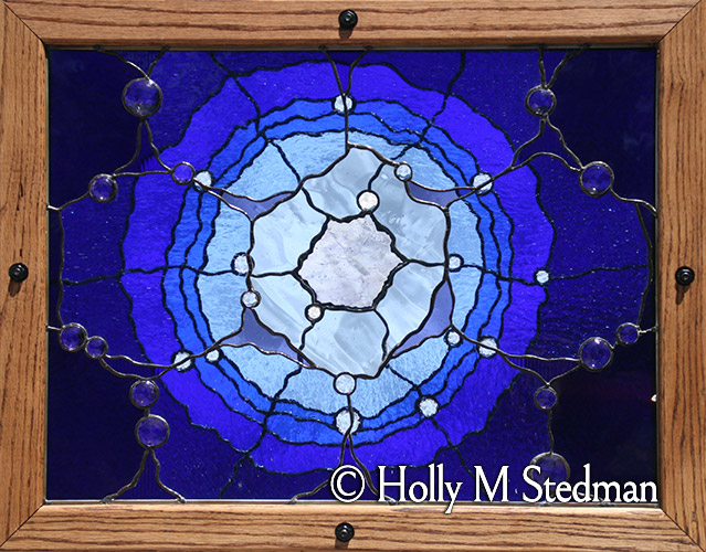 Framed, multilevel stained glass panel with transparent abstract flower design