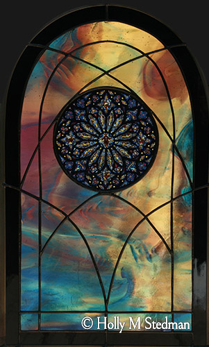 Arch-shaped stained glass panel with an inner intricate circular design
