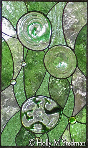 Green stained glass panel with flowing, geometric design