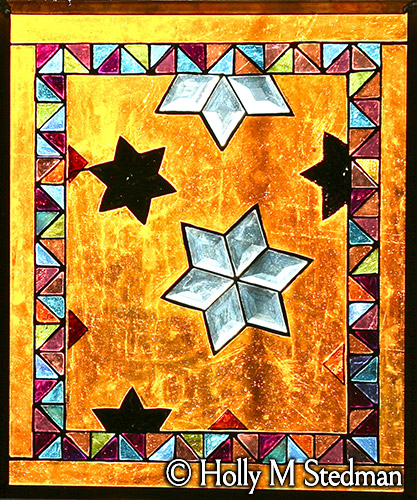 Stained glass panel with stars and geometric border