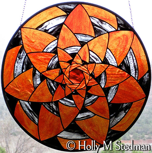 Circular stained glass panel with spiral design