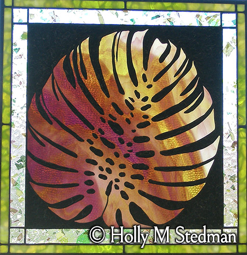 Stained glass panel with an imprint of an exotic leaf