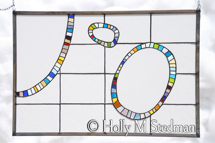 Stained glass panel of ovals with brightly colored borders