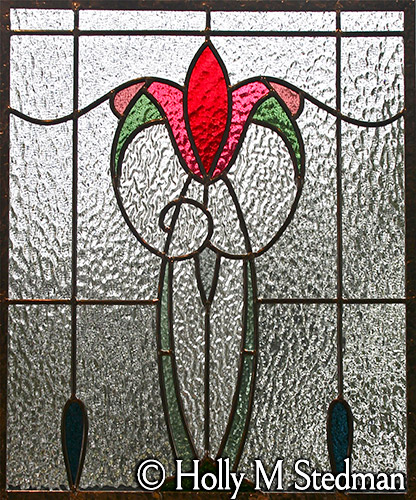 Geometric stained glass panel of red flower with textured glass